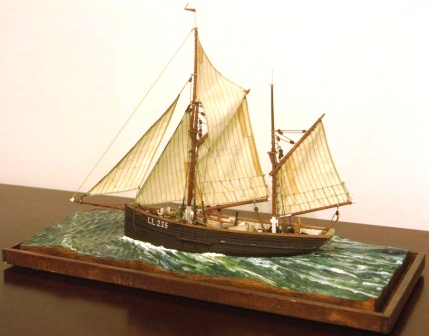 Maria LL225. North Sea fishing cutter with set sails. Depicting a busy crew handling freshly caught herring on deck. 20th century model. Mounted in a glass case.