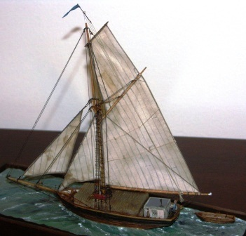 Sofia av Länna. Archipelago cargo boat with set sails and including crew members and a load of timber logs. 20th century model. Mounted in a glass case.