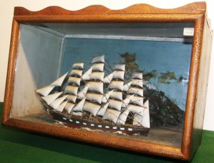 19th century sailor-made diorama depicting a four-masted barque with set sails. Decorative background with mountainous coastline, village and lighthouse.