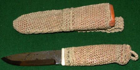 Knife with handforged steel-blade carrying initials J.A. Handle and leather sheath coated with rope and copper-thread.