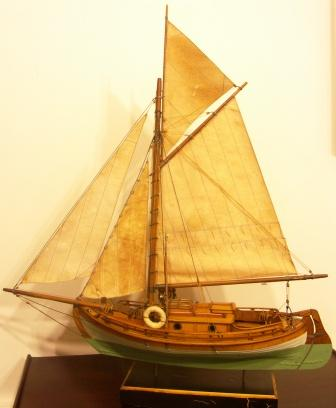 Gaff-sail rigged cabin boat with set sails. 20th century model.